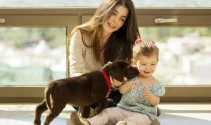 Dog boarding, mother and daughter playing with puppy.