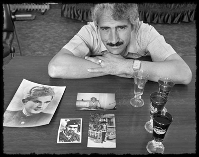 Ali son with photos of dad