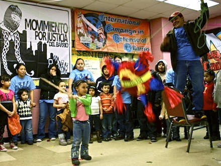 "A young girl breaking the ""neoliberal piñata"" at the end of one of the Movement for Justice in El Barrio's encuentros, gatherings that were inspired by the Zapatistas. (Flickr / Michael Gould-Wartofsky)"