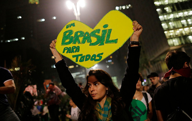"A woman holds up a heart-shaped sign that reads in Portuguese ""One Brazil for all,"" on Paulista Avenue where crowds gathered to celebrate the reversal of a fare hike on public transportation, in Sao Paulo, Brazil, Thursday, June 20, 2013. (Flickr/Sebástian Freire)"
