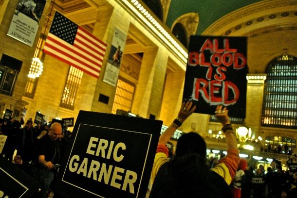 "Activist holds up a sign reading ""All Blood Is Red"" in Grand Central on Martin Luther King Day. (WNV/Peter Rugh)"