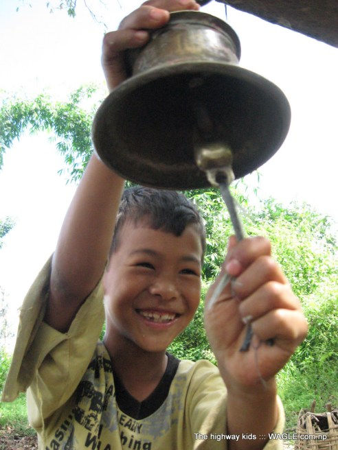 highway kids of nepal. kid playing a bell
