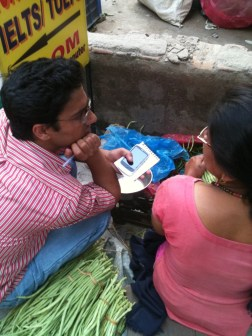 A reporter in conversation with a vegetable vendor
