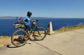 A cyclist crossing the camino 0.0km marker Finisterre Spain