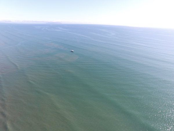 Fishing vessel 63018 working very close to shore, aerial view.