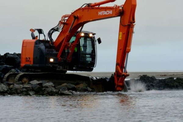 A digger scoops rocks out of the river.