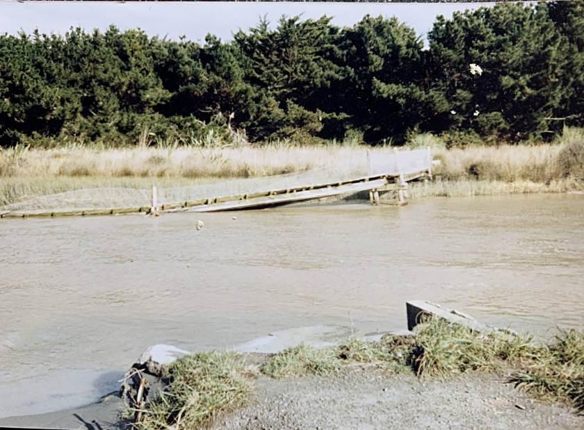 Rickety old footbridge sunk in the stream.