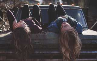 two girls sitting on back of a truck