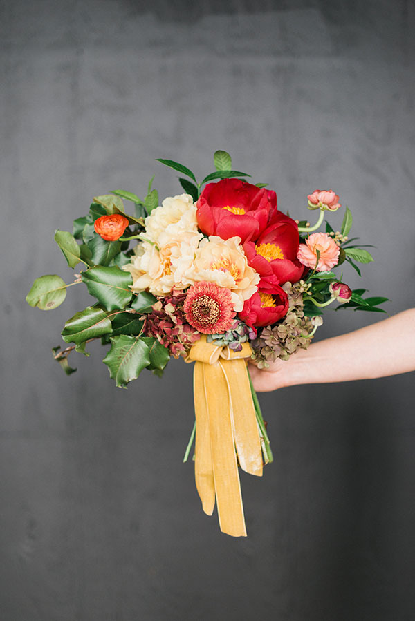 Red and orange bridal bouquet by Martha McIntosh and Waiting on Martha for The Celebration Society. Rustic White Photography
