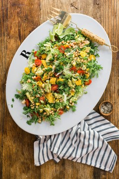 Frisee salad with avocado, cherry tomatoes, grilled corn and beans