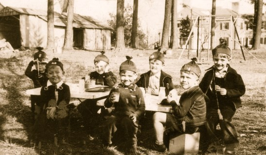 Children sitting at a table drinking milk.