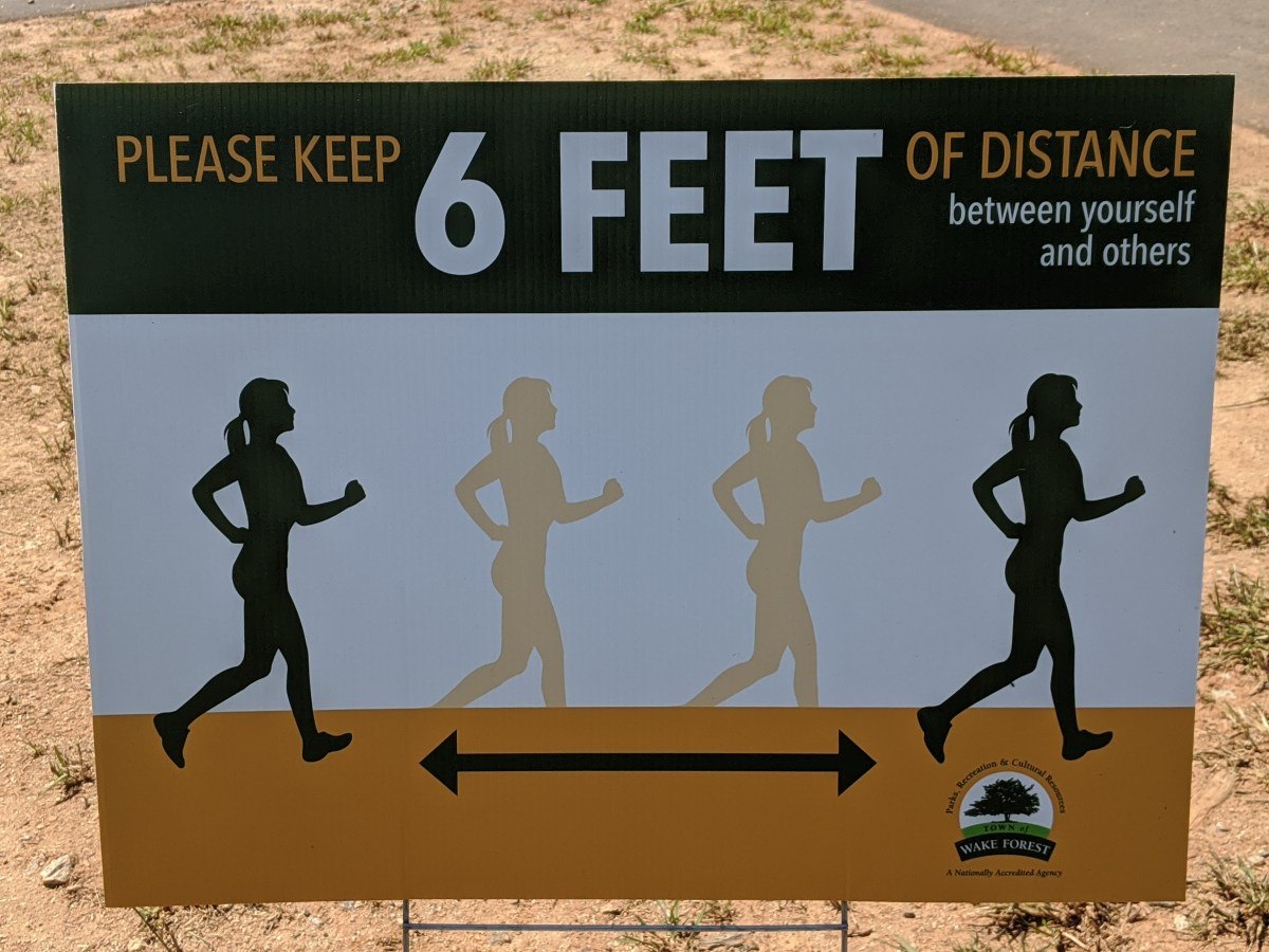 """Photograph of sign reading """"Please Keep 6 FEET of Distance between Yourself and Others."""""""