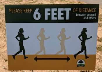 "Photograph of sign reading ""Please Keep 6 FEET of Distance between Yourself and Others."""