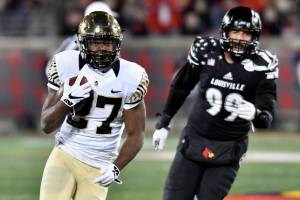 Wake Forest's Tyler Bell (27) is pursued by Louisville's James Hearns (99) during the first half of an NCAA college football game, Saturday, Nov. 12, 2016, in Louisville, Ky. (AP Photo/Timothy D. Easley)