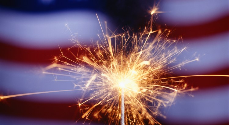 Sparkler with American flag in background, (Close-up)