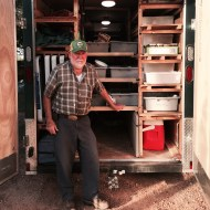Joe Montague of Homeplace Farm stands in front of their customized trailer, designed by Joe to transport all of their canned items to farmers' markets.