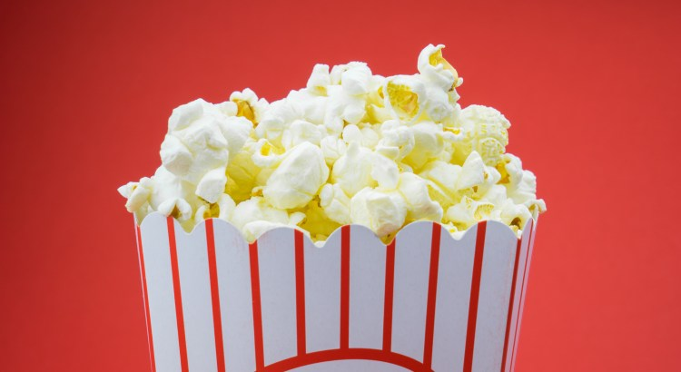 Classic box cinema popcorn on white background in studio shot.