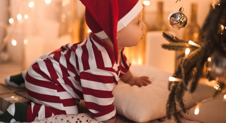 Baby girl 1 year old crawling under Christmas tree wearing body suit in red and white color. Looking at Christmas ball and see her reflection. Holiday season.