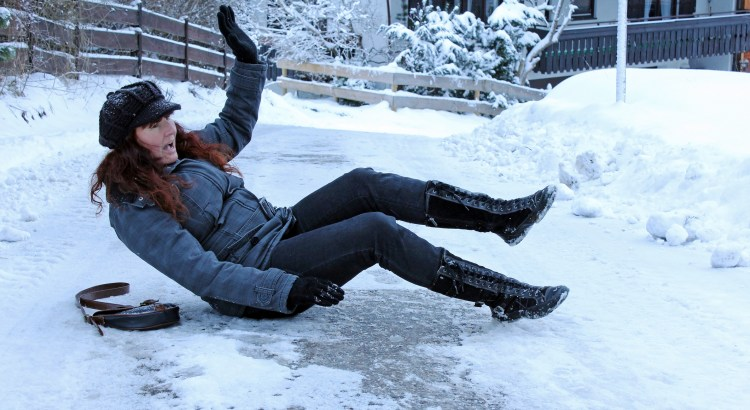 a woman slips on snowy-smooth street