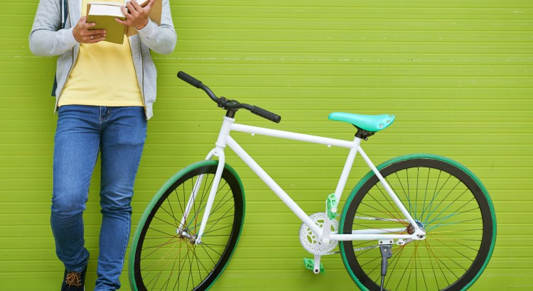 Cropped image of college student standing next to his bicycle and reading a book