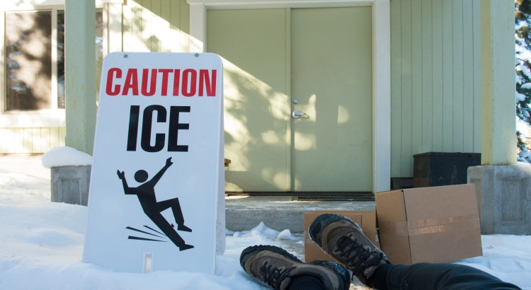 This image illustrates a situation where a delivery person with boxes has slipped in spite of a sandwich board warning of icy conditions. Only lower legs and feet are shown of the delivery person.