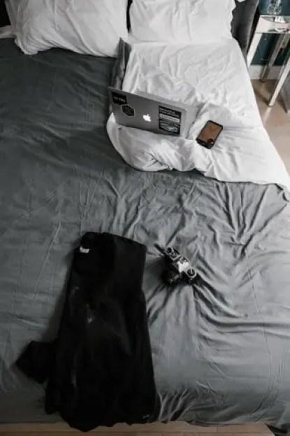 black-jacket-beside-camera-on-bed-3201767