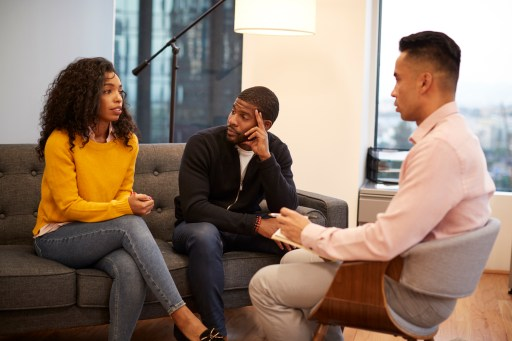 Woman Sitting On Couch Meeting With Male Relationship Counsellor In Office