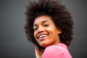 woman smiling against gray background