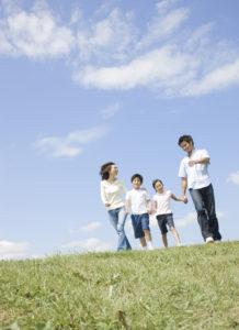 青空のもと、仲良く歩く家族