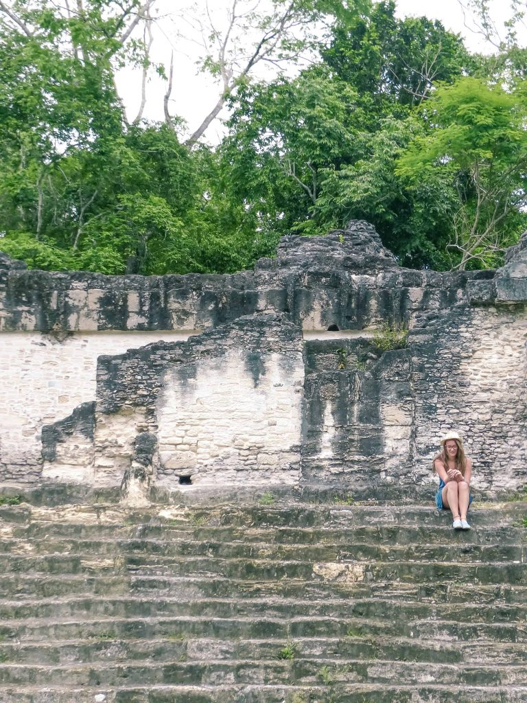 sitting on the steps of tikal pyramid