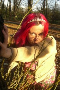 A woman with pink hair is leaning on a tree. She is White and is wearing a gold coloured cardigan, a floral dress and a tiara. It is Autumn and the light is glowing