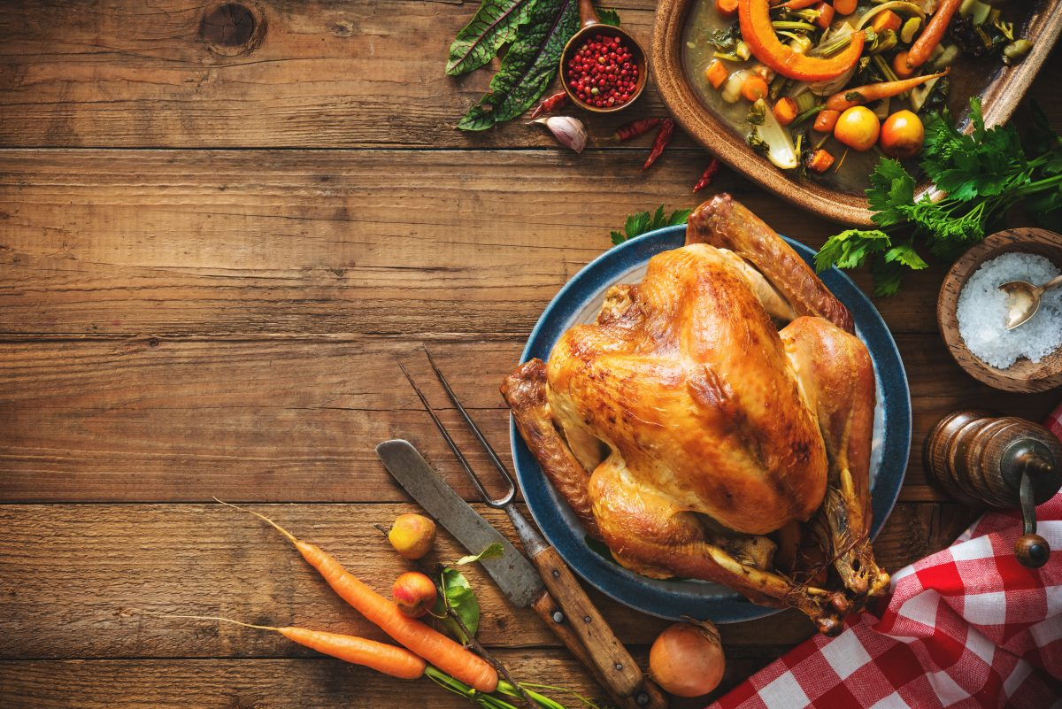 Thanksgiving turkey on rustic wooden table with side dishes