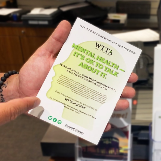 Gun store employee showing mental health flyer from WTTA to customer