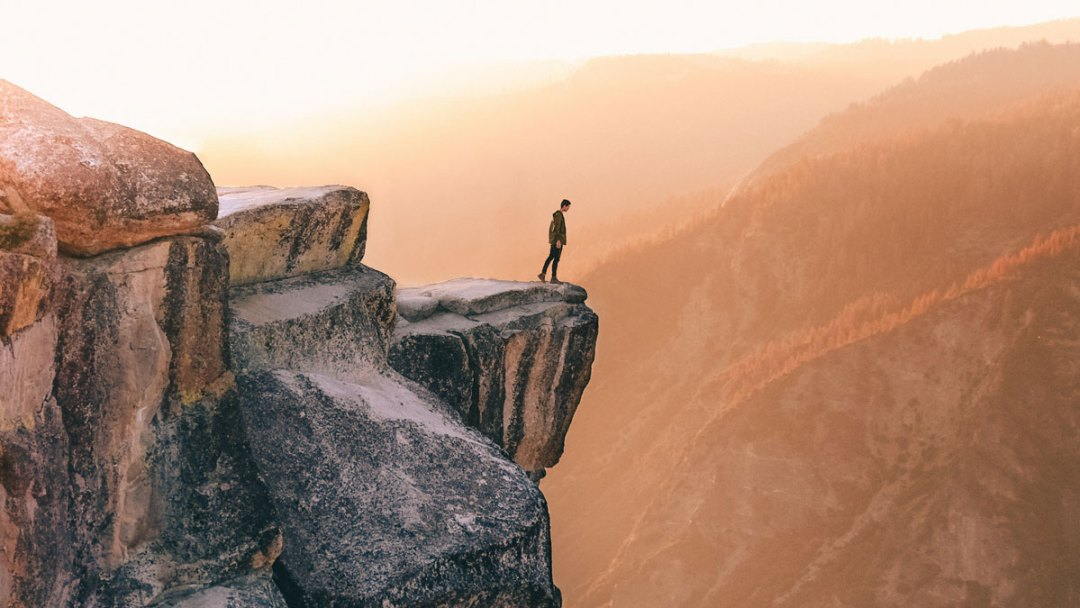 A person looks down over a large cliff, ready to step away from the edge