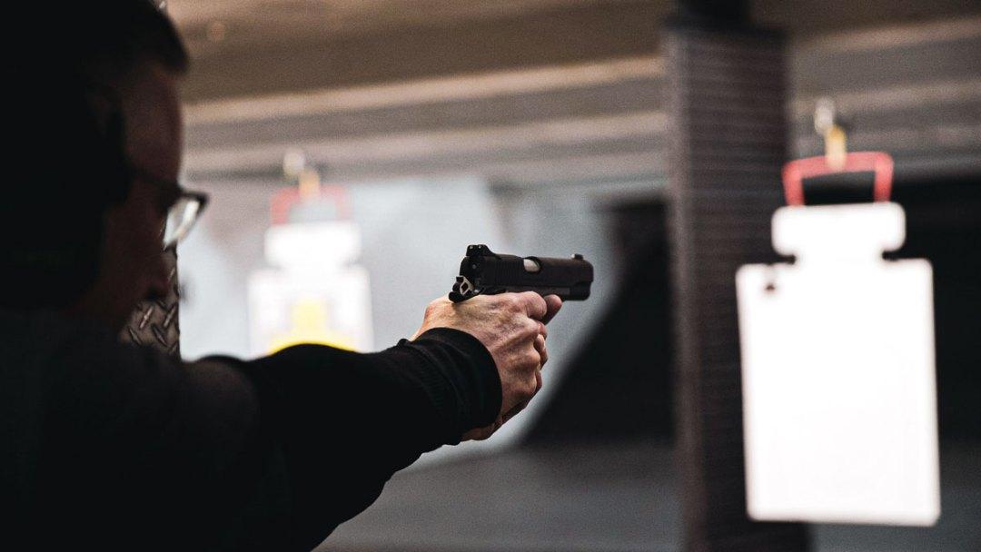 Man at shooting range firing a pistol