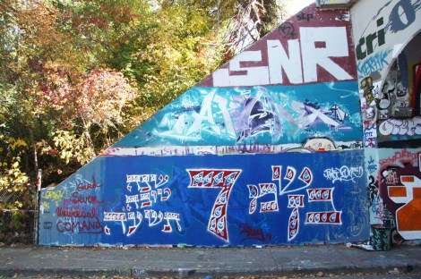 Unidentified (bottom), Apashe (middle), SNR (top) at the Rouen tunnel legal graffiti wall