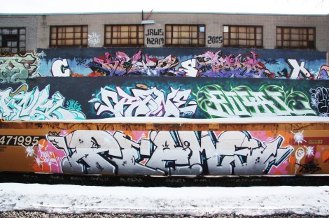 Graffiti by Peams-CSX on parked train. Also visible on the background wall is graffiti by Crane, Royal and many others.