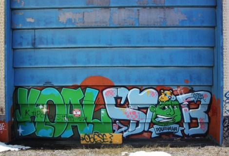 Koal and Snob graffiti on garage door of abandoned warehouse