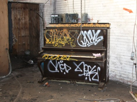 tagged piano in the abandoned Transco; tags include Nock for RCD, Rizek, Resok, Meth.