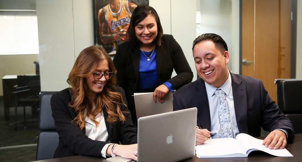 Three employees laughing and looking at a computer