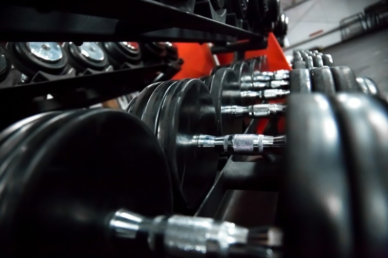 Weight training equipment, row of steel sports dumbbells in sports club