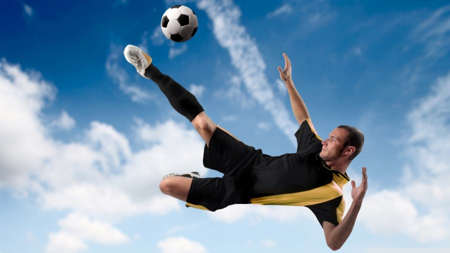 Football player in air kicking ball