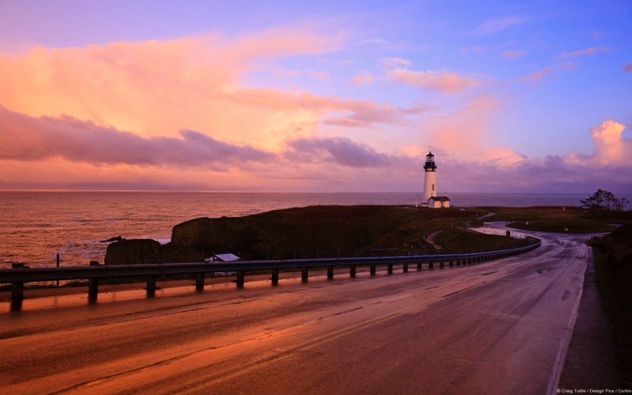 A road and lighthouse along the Oregon Coast at sunset