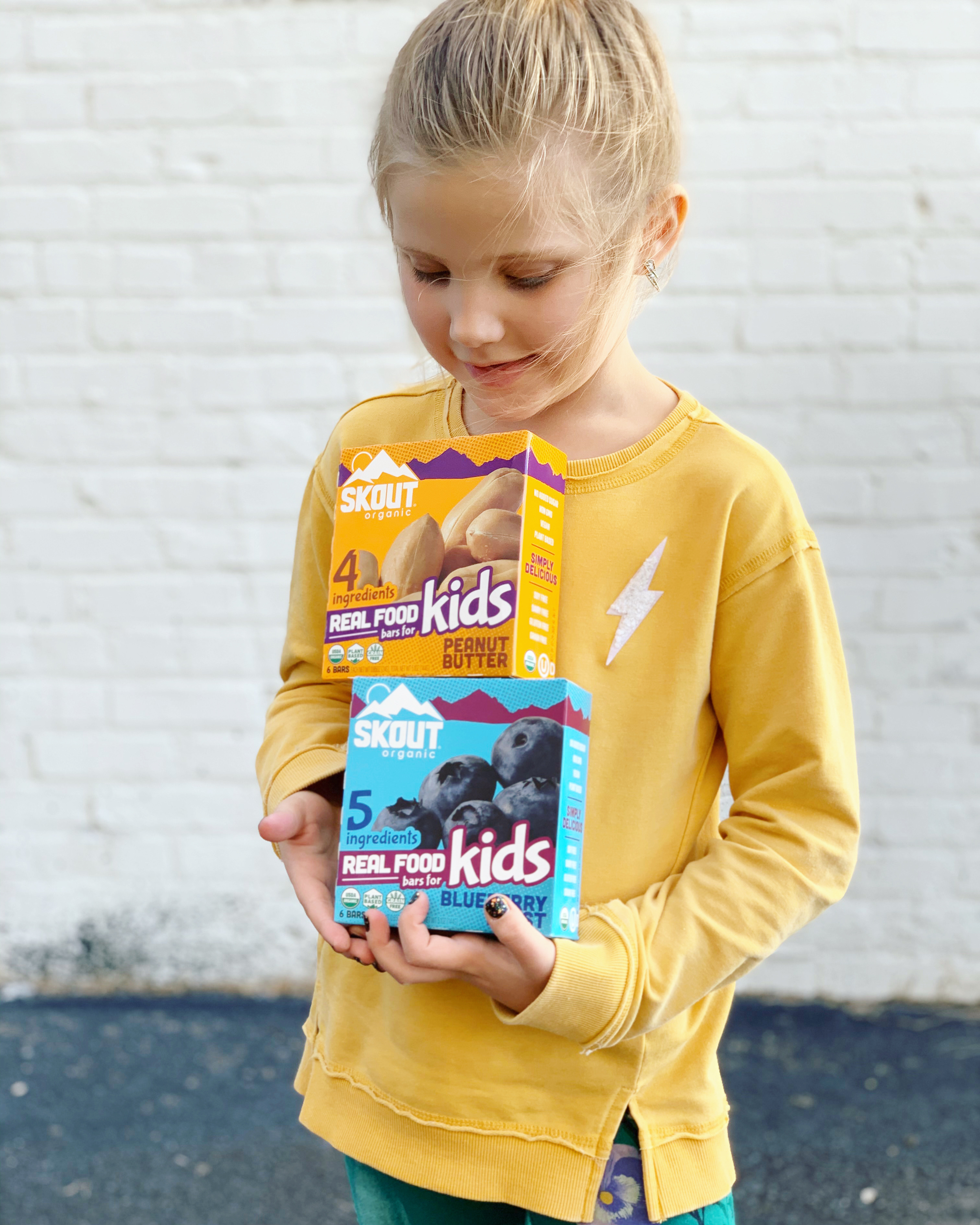 child holding skout organic protein bars