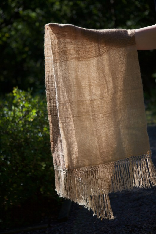 An arm holding up a sheer woven shawl in natural colours.