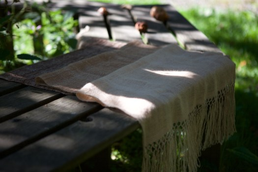 A sheer woven shawl folded over a park bench