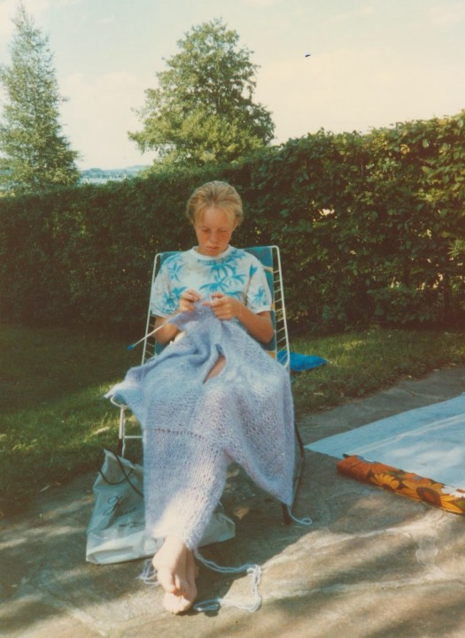 Josefin Waltin knitting a pastel purple sweater in a garden chair 1985.