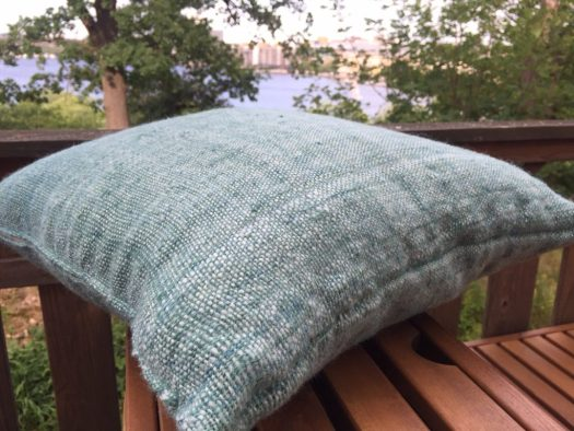 A hand woven pillowcase. Lake in the background.
