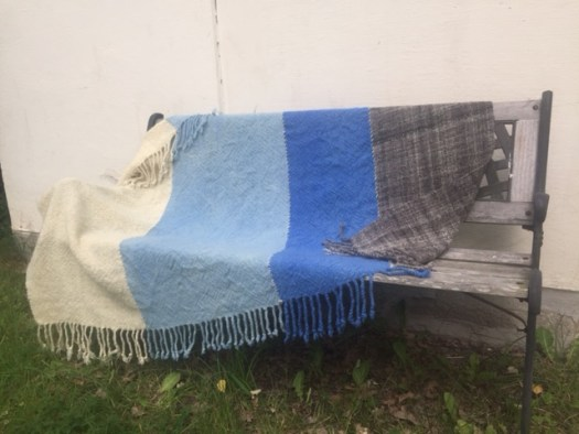 A woven wool blanket draped over a park bench.