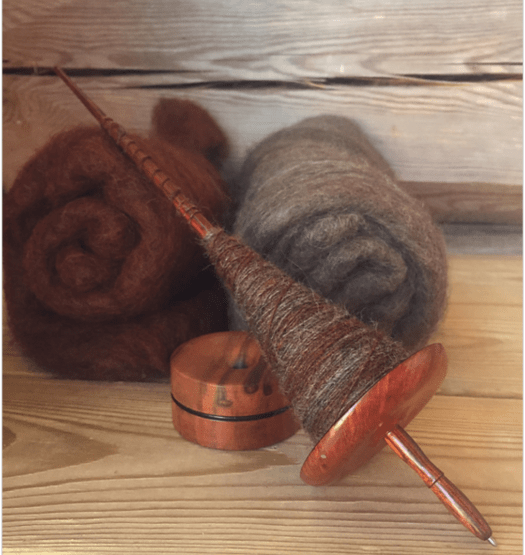 A support spindle filled with yarn, Carded batts in the background.
